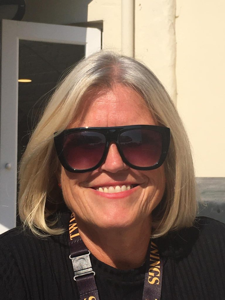 Julie Neilson has blonde shoulder length hair, black sunglasses and is smiling. She is wearing a black top and a Twinnings lanyard.
