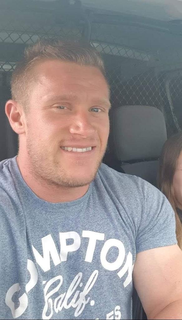 Ryan has short, styled blonde hair, he is sat in a car or van in a grey short sleeved t-shirt.