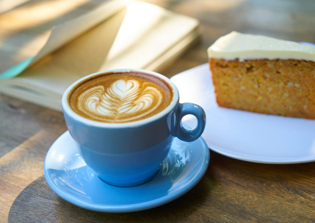 A stock image photo of a light blue coffee cup and saucer, a slice of cake (looks like carrot cake - yum!) and a book with a blue cover slightly blurred in the background.
