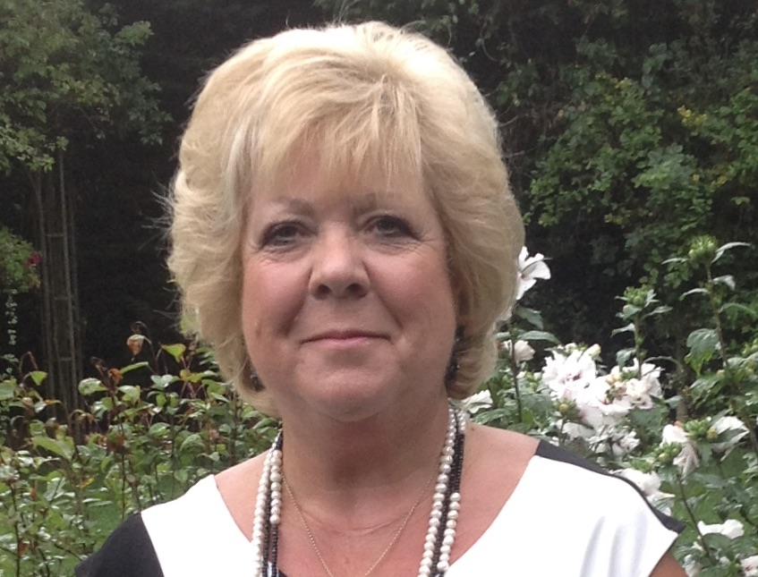 Sally has short blonde hair just below earlobe length. She is smiling in a garden in a black and white top with a string of black and white beads around her neck.