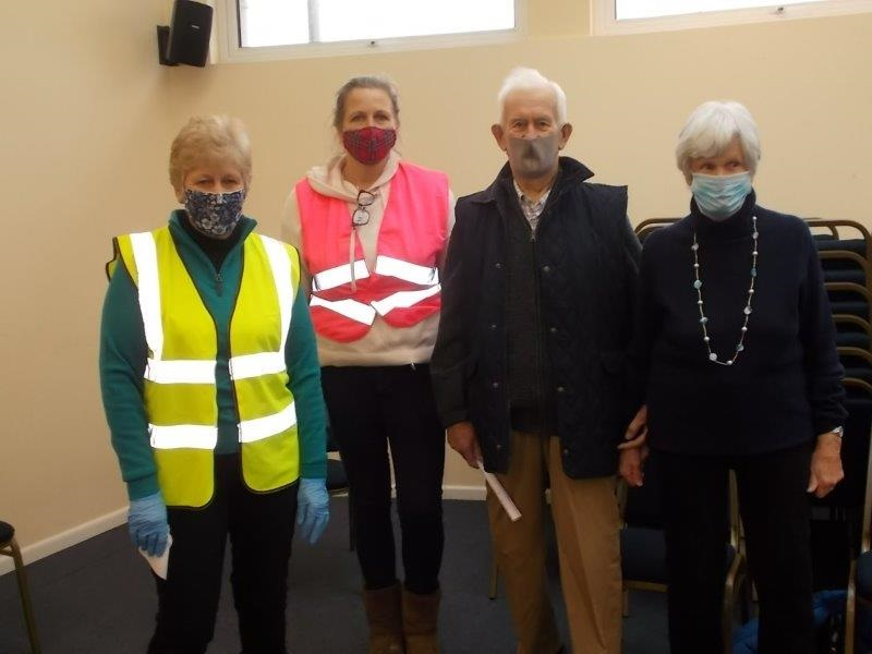 2 covid volunteers pictured with an older lady and gentleman after receiving their jabs. Everyone has masks on and the 2 covid volunteers are wearing hi-vis.