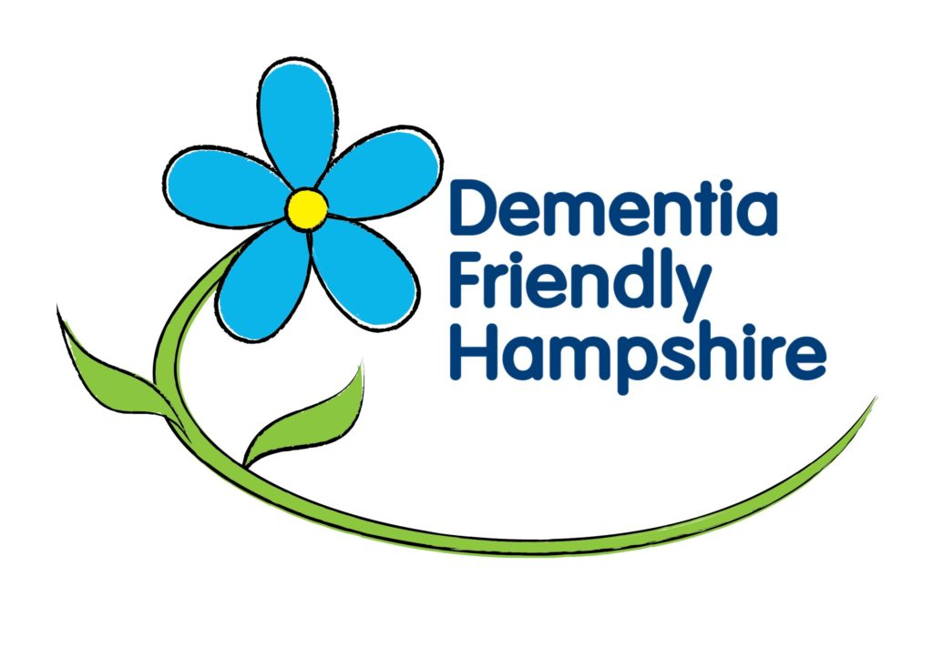 Dementia Friendly Hampshire's logo. It has blue text and a blue flower with a yellow centre to the left with the stem curving round underneath the text.